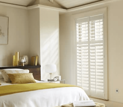 bedroom shutters with yellow bedding